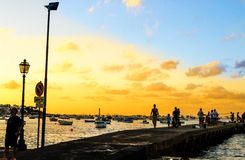 The quay at dusk. People fish and walk along a quay at sunset Stock Photography