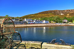 Quay with fish traps and bollard in the foreground and waterfront houses in the background Stock Photography