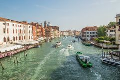 Quay of a Grand channel with cargo boats, river trams, boats. Along the canal there are Venetian houses. stock photo