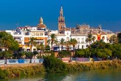 Quay of Guadalquivir and Giralda, Seville , Spain. Quay of the river Guadalquivir, Plaza de toros de la Real Maestranza de Caballeria and Giralda in the sunny stock photography