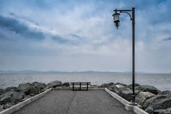 Quay. With lamppost, bench and rocks on a dark blue sky stock photo