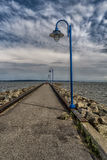 Quay. With lamppost rocks and dark blue sky stock image