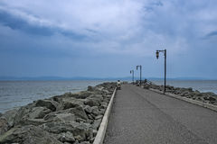 Quay. With lamppost rocks and dark blue sky stock photo
