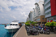 Quay in Male Maldives with Boat and Motorcycles. Quay in Male Maldives with Boat docking on clean blue turquoise water and Motorcycles parking Royalty Free Stock Images