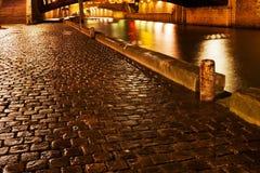 Quay in Paris at night. Wet cobblestone pavement quay in Paris at night Royalty Free Stock Image
