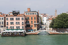 Quay, restaurant and bridge over channel in Venice Stock Photos