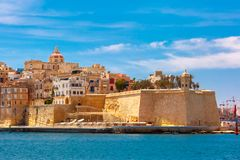 Ancient fortifications of Valletta, Malta. Quay of Valletta with traditional Maltese building with colorful shutters and balconies in the sunny day, Valletta Royalty Free Stock Images