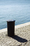Quayside bollard. A view of a short, cylindrical metal post permanently attached to a pier or quay, often called a bollard to which a ship is tied while docked Royalty Free Stock Images
