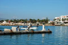Quayside in Caleta de Velez harbour. Fishing boat entering harbour with fisherman on the quayside in the foreground, Caleta de Velez, Malaga Province, Andalusia Stock Images
