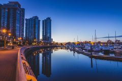 Quayside Marina before Sunrise. Cityscape from Quayside Marina taken before sunrise with reflections of buildings and boats in the calm water, Vancouver, British stock image