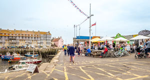 Quayside Restaurants. A small group of outdoor restaurants situated on the quayside, next to the harbour.  Numerous people including  families with children are Stock Images