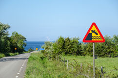 Quayside road sign at country road. Road sign with warning for quayside at a country road by the Baltic Sea in Sweden Stock Photos