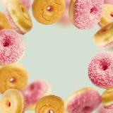 Que cai ou o rosa filhóses vitrificadas de voo com polvilha no movimento no fundo azul pastel Imagens de Stock Royalty Free