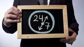 24 a 7 que dibujan en la pizarra, hombre de negocios que lleva a cabo la muestra, concepto del tiempo del negocio Imagenes de archivo