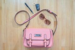 Que sai de um saco aberto? As chaves, os óculos de sol e as penas do carro das mulheres saíram de uma bolsa cor-de-rosa Fotos de Stock
