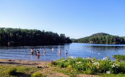 A group of people swimming in a beautiful pristine lake off of the autoroute de la gatineau in the Outaouais region, Quebec stock photography
