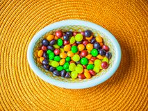 A bowl of candies on an orange placemat. QUEBEC, CANADA - March 13, 2018: This image depicts sweets of all colors in a beautiful bowl Stock Images