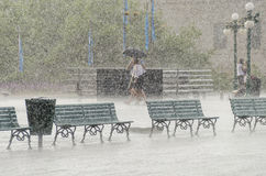 Quebec City, Canada - July 27, 2014: Couple walking in heavy rain with umbrella on boardwalk street close to Chateau Frontenac. Royalty Free Stock Photography