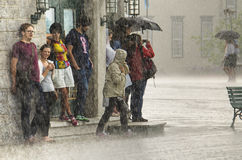 Quebec City, Canada - July 27, 2014: A group of people hide from heavy rain under a building. Stock Photo