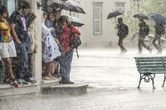Quebec City, Canada - July 27, 2014: A group of people hide from heavy rain under a building while three walk with umbrellas Stock Photos