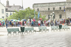 Quebec City, Canada - July 27, 2014: People with umbrellas walking in heavy rain on boardwalk street close to Chateau Frontenac Stock Image