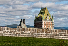 Quebec City with Chateau Frontenac. A view of Chateau Frontenac from the Citadelle of Quebec City, with the hiolls and a few clouds in the background Stock Photo