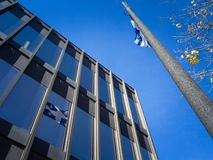 Quebec flag reflecting in a business financial skyscraper tower waiving in the air. stock images