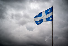 Quebec Flags Waves Before Stormy, Cloudy Skies stock photography