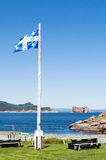 Quebec Provincial Flag. This is a picnic area on Ile de Bonaventure. In the background is Pierced Rock, Perce, Quebec, Canada and the Gulf of St. Lawrence Stock Photography