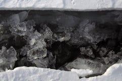 A quebra fresca quebrou o gelo grosso A agua potável fresca aumenta das profundidades e do gelo no frio Tempestade de gelo Foto de Stock
