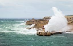 Quebra-mar e farol do leste de Ricasoli para suportar o mar cru e ondas altas imagem de stock royalty free