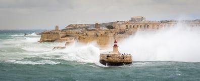 Quebra-mar e farol do leste de Ricasoli para suportar o mar cru e ondas altas imagens de stock royalty free