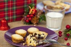 Quebrado pique la empanada y la leche en una tabla de la Navidad Imagen de archivo