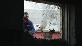 Quebrando uma parede com um malho Tijolos de queda Um trabalhador que veste vidros protetores e macacões azuis Vista de filme