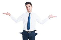 Quebrou o vendedor que mostra bolsos de calças vazios imagens de stock royalty free