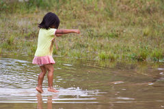 Quechua girl jumps playfully in water. Puyopungo, Ecuador - January 7, 2012 - An indigenous Quichua girl jumps playfully in water. The Quichua are the largest of Stock Photography