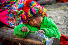 Quechua girl playing with bottle in a village in the Andes, Olla Royalty Free Stock Photos