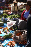 Quechua Indian women bargain and sell vegetables > Royalty Free Stock Images