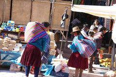 Quechua Indian women bargain and sell vegetables > Stock Photo