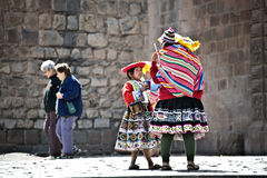 Quechua Indians break from posing with tourists Royalty Free Stock Photos