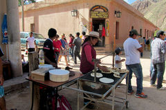 Quechua woman cooking bread at the market Royalty Free Stock Photography