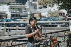 KYOTO, JAPAN, SEPTEMBER 14, 2017: A Quechuan man playing a pinkullo in a Kyoto street. The wood instrument is similar to a flute royalty free stock image