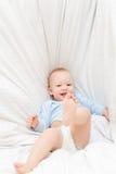 Queda alegre pequena do bebê na cama foto de stock royalty free