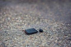 Queda da chave do carro na estrada asfaltada O motorista perdeu suas chaves do ve?culo imagens de stock