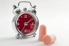 Queda da dificuldade adormecida, problemas do sono e insônia  devido ao ruído alto com um despertador e um par de tampões de ouvi foto de stock