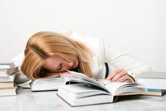 Queda da mulher nova adormecida ao estudar Foto de Stock Royalty Free