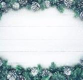 Queda de neve na árvore de abeto do Natal com a decoração do ramo do pinho na madeira branca fotografia de stock