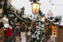 queda de neve no mercado do Natal com lâmpadas e decoração das luzes dentro fotos de stock royalty free
