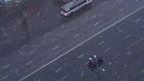 Queda de neve sobre a rua da cidade com carros vídeos de arquivo