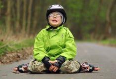 Queda do menino em patins de rolo Imagens de Stock